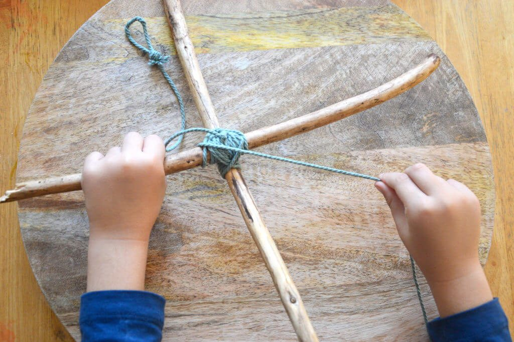 Child-winding-cord-around-sticks-in-x-shape-for-nature-mobile-1024x681.jpg#asset:13579